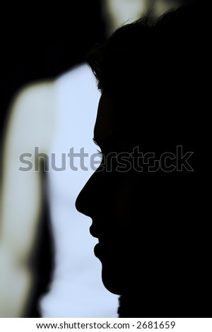 nightlife : woman outdoor in a  city  on shopping tour,  profile of her passing by a shop with man model - stock photo