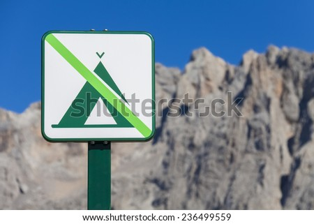 """""""No camping"""" sign post in front of a mountain range at Picos de Europa (Spain). - stock photo"""