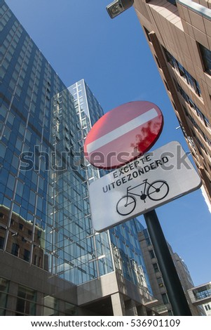 """No entry except for cyclists"" sign in French on city street, with modern blue office building in the background"