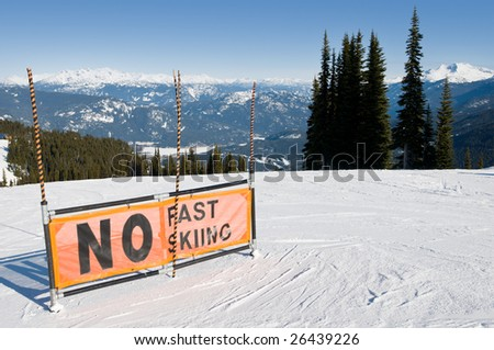"""""""No fast skiing"""" warning sign on ski trail, panoramic view from top of mountain - stock photo"""