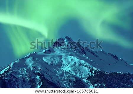 Northern Lights over snowy mountain - stock photo