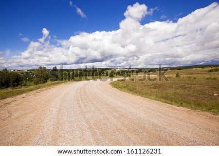 not asphalted rural road which is passing across the field - stock photo