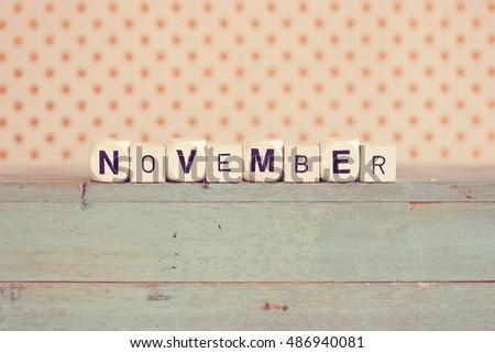 """NOVEMBER"" printed on dice against rustic wood background with polka dots"