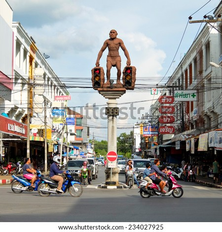29 November, 2014: Street art, Statue of Neanderthal man, unusual traffic lights in Krabi town, Thailand - stock photo