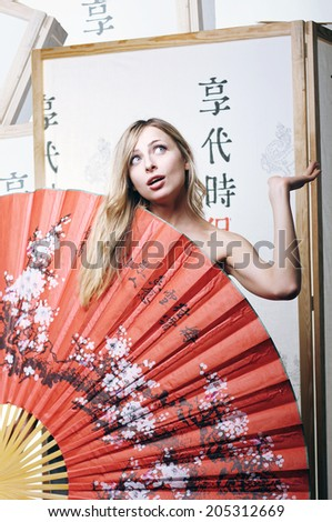 Nude geisha hiding behind red fan - stock photo