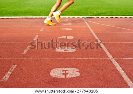 Number lanes track and athlete running on number lanes, soft focus and blur - stock photo