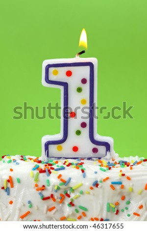 Number one birthday candle on green background - stock photo