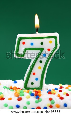 Number seven birthday candle on green background - stock photo