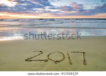 2017 numbers written on a sand beach during sunset - stock photo