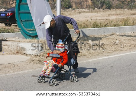 12 OCt,2014 Beijing China.  Chinese grandpa babysitting and take care of grandson with baby stroller on road
