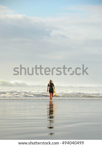 3 October, 2016, Auckland, New Zealand: A surfer is walking with a surf in his hands across the sea shore.