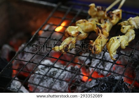 octopus grilling and BBQ flames, Thailand - stock photo