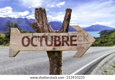 """""""Octubre"""" (In Spanish: October) wooden sign with a street background  - stock photo"""