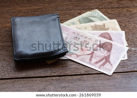 1000,5000 of Korea Won on old wooden plank with wallet - stock photo