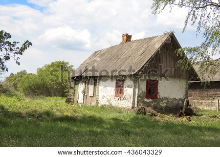 Old abandoned farmhouse near blooming trees against the bright spring sky - life goes on.
