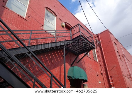 old brick building with fire escape stairs and cloudy sky