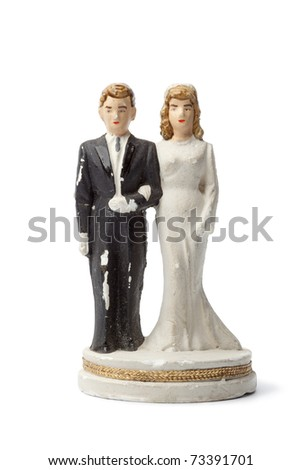 Old damaged plaster bride and groom cake topper isolated on white background - stock photo