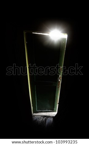 Old dark room with shining closed door. Sip of light from green glass metaphor - stock photo