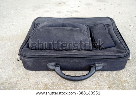Old dusty laptop bag on cement background - stock photo
