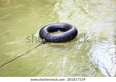 old inner tube on river - stock photo