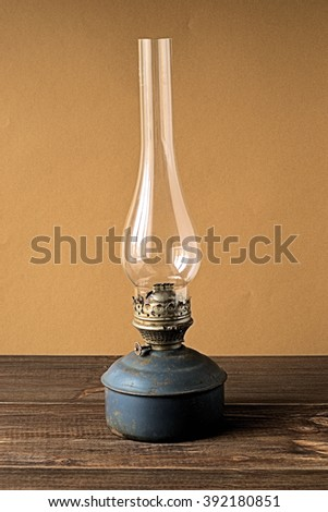 Old kerosene lamp on a brown background.