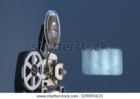 old movie projector with screen - stock photo