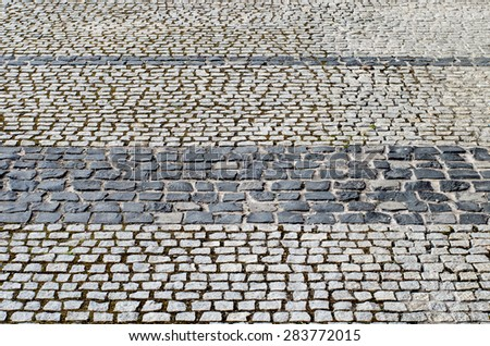 old road paved with black and grey granite stones
