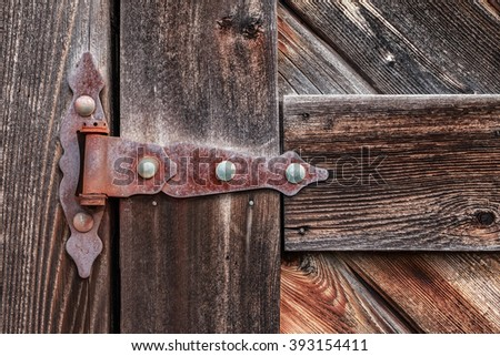 Old rusty hinge on wooden weathered door. - stock photo