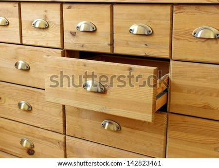 old wooden  antique chest of drawers  with metal handles, open drawer - stock photo