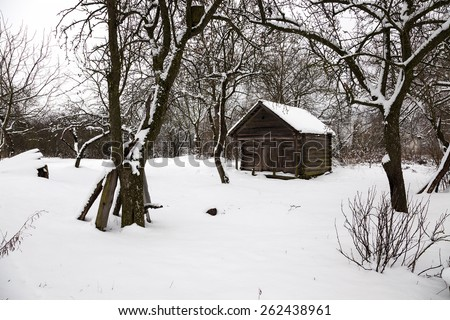 old wooden outbuilding in the countryside in winter - stock photo