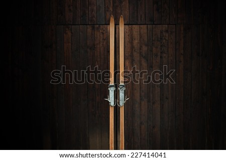 Old wooden skis leaning against a wooden wall - stock photo