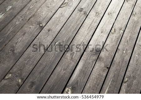 Old wooden surface made of a number of boards, located outdoors. Part of the building for the rest. Photo taken closeup. Visible damage and dirt.