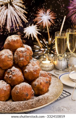 'Oliebollen', traditional Dutch pastry for New Year's Eve. With champagne and fireworks in the background. - stock photo
