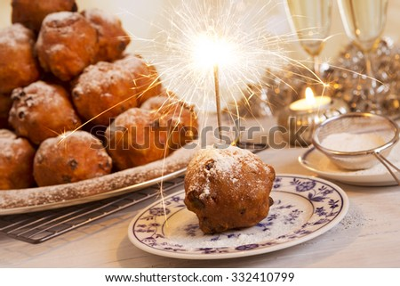 'Oliebollen', traditional Dutch pastry for New Year's Eve. With champagne and sparklers in the background. - stock photo
