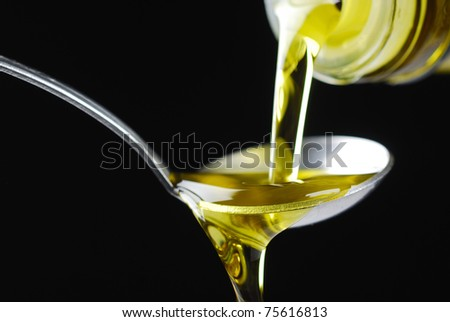 olive oil being poured onto a spoon - stock photo