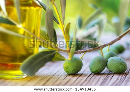 olive oil on old wooden table and an olive branch  - stock photo