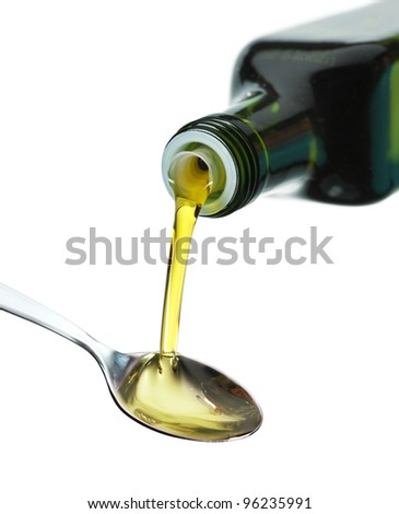Olive Oil pouring from a bottle to spoon - stock photo