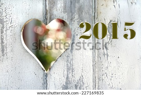 2015 on a old door with a a heart pierced  - stock photo