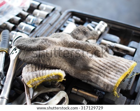 on duty dirty glove with car engine with tools  - stock photo