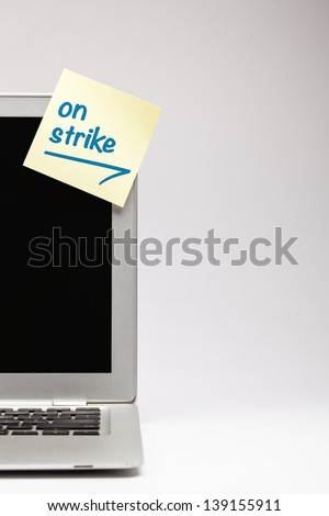 """on strike"" written on sticky note, on laptop screen. - stock photo"