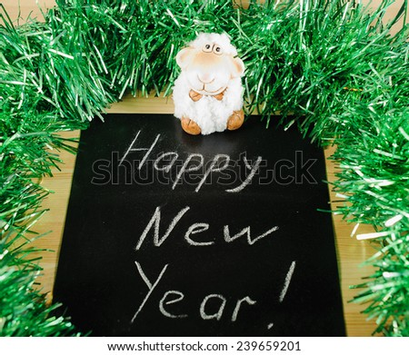"on the black Board, white chalk written ""happy new year"" on the background of green tinsel and white sheep - stock photo"
