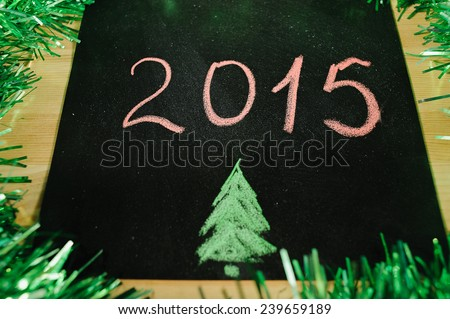 on the black Board with red chalk written 2015 against the green tinsel - stock photo