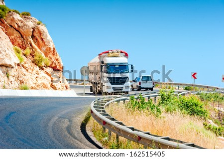 oncoming traffic truck and a car in the mountains - stock photo