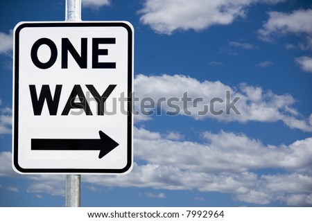 """One Way"" street warning sign against a blue sky background - stock photo"