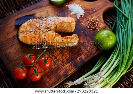 ?ook restaurant cooked a salmon steak on the grill and served with him a piece of lemon, onion, few tomatoes. Fish lying on a wooden surface, close to her small tomatoes on a branch, onion and lime - stock photo