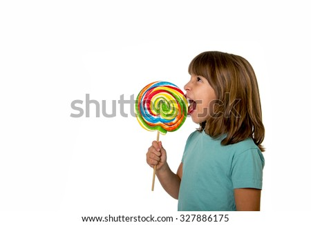 4 or 5 years old child girl eating big multicolor spiral lollipop candy isolated on white background in children love sweet and sugar concept and dental health and care concept with copy space - stock photo