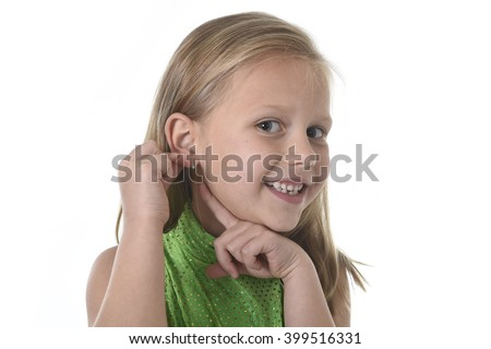 6 or 7 years old little girl with blond hair and blue eyes smiling happy posing isolated on white background pointing ear in language lesson for child education and body parts school chart set - stock photo