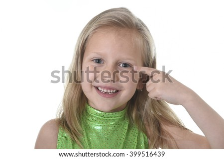 6 or 7 years old little girl with blond hair and blue eyes smiling happy posing isolated on white background pointing eye in language lesson for child education and body parts school chart set - stock photo