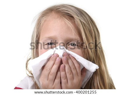 7 or 8 years old sweet and cute blond hair little girl blowing her nose with paper tissue having a cold feeling sick in child winter flu health care concept isolated on white background - stock photo
