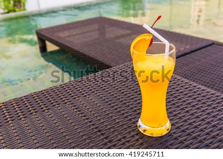 Orange juice on the table at the pool. - stock photo